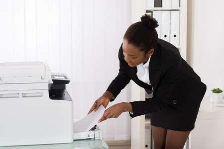 fotocopiadora: Empresaria africana Inserción de documentos de jóvenes en la máquina de la fotocopia En La Oficina Foto de archivo