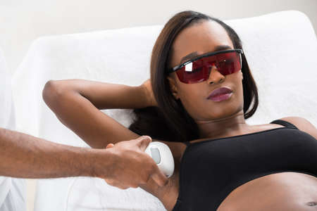 Therapist Removing Hair Of Young African Womans Armpit With Epilator Stock Photo