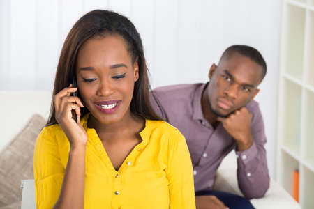 black guy: Young Man Looking At Woman Talking On Cellphone At Home