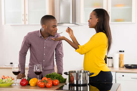 food testing: Photo Of Young Man Testing Food In Kitchen Stock Photo