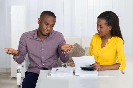 Junge afrikanische Paare streiten über Bill zu Hause Standard-Bild