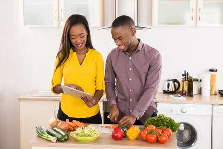 black couple: Young African American Couple In Home Kitchen Using Electronic Tablet