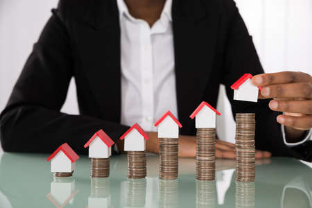 Close-up der Geschäftsfrau Hand Arranging Haus-Modell auf gestapelten Münzen am Schreibtisch