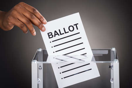 hand paper: Close-up Of A Person Hand Inserting Ballot In Glass Box Against Gray Background Stock Photo
