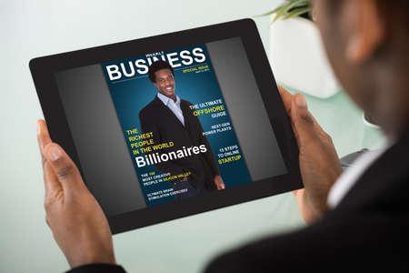 Primer plano de una joven empresaria lectura revista en línea En Tableta digital Foto de archivo