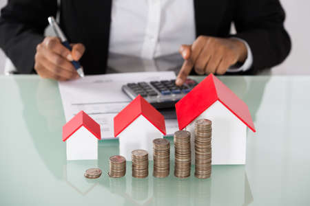 Close-up Of Businesswoman Calculating Invoice With Stacked Coins And House Models On Desk Stockfoto