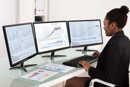Młoda Afrykańska bizneswoman analizuje dane Na Wieloskładnikowym ekranie komputerowym W biurze Zdjęcie Seryjne