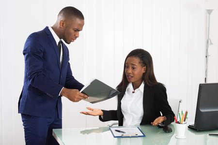acoso laboral: Infeliz Young Boss muestra el documento a su Trabajador de sexo femenino en oficina Foto de archivo
