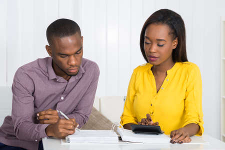 retirement homes: Photo Of Young Couple Calculating Bill At Home