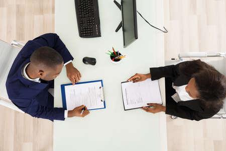 persone nere: Inquadratura alta di due uomini d'affari che lavorano in ufficio Archivio Fotografico