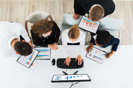 business chart: Group Of Multiracial Businesspeople Working On Graphs In Office