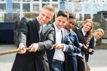 Gruppe Glückliche Multiethnic Menschen spielen Tauziehen