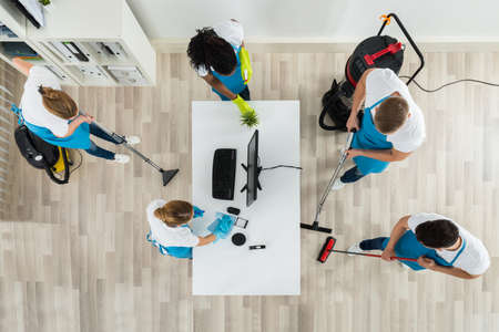 top angle view: Group Of Janitors In Uniform Cleaning The Office With Cleaning Equipments