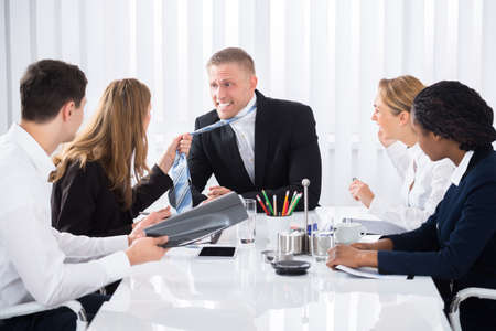 Businesswoman Pulling Businessman's While Quarreling In Meeting