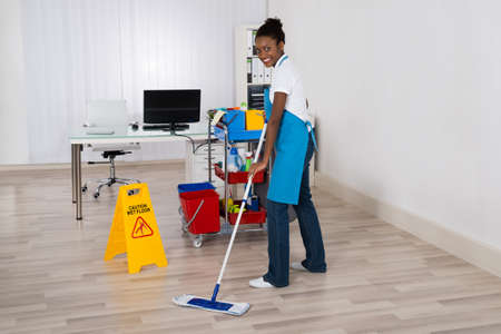 janitor: Female Janitor Mopping Wooden Floor With Caution Sign In Office Stock Photo
