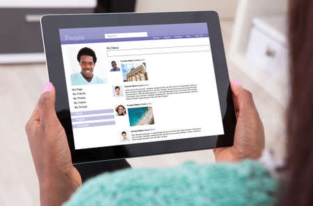 community people: Close-up Of A Woman Using Social Networking Site On Digital Tablet Stock Photo
