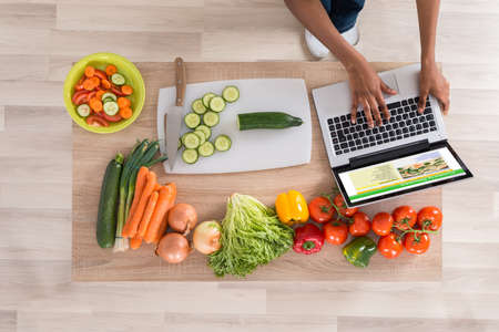 kitchen device: High Angle View Of Woman Looking At Recipe On Laptop In Kitchen Stock Photo