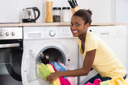 Young African Woman Putting Clothes Into Washing Machine At Home
