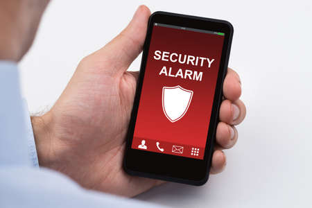 breach: Close-up Of Businessperson Holding Mobile Phone Showing Security Alarm Stock Photo