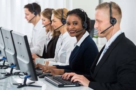 centre: Young African Businesswoman With Headset Working With Other Colleagues In Call Center