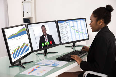 gantt: Young African Businesswoman Working With Multiple Computer Screen Stock Photo