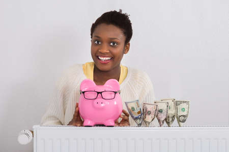 smart investing: Portrait Of A Smiling Young African Woman Holding Piggy Bank Near Banknotes