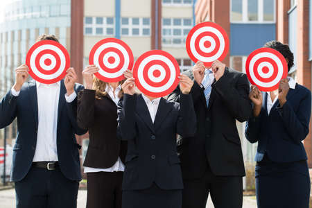 hiding face: Group Of Professional Businesspeople Hiding Face With Red Dartboard