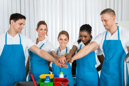 team hands: Group Of Happy Cleaners In Uniform Stacking Hands At Workplace