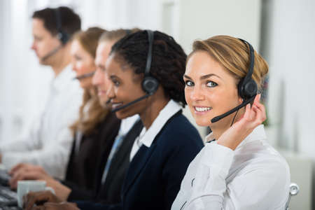 call girl: Call Center Operators In A Row Working On Computers In Office
