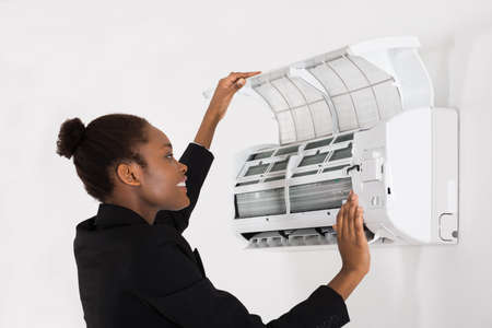 humidifier: Young Happy African Businesswoman Checking Air Conditioner In Office Stock Photo