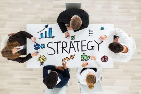 Équipe de professionnels dessinant un diagramme de stratégie avec un marqueur