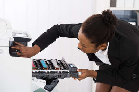 copier: Young Businesswoman Fixing Photocopy Machine In Office Stock Photo