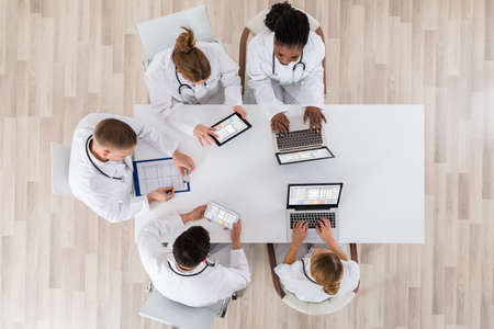 High Angle View Of Doctors With Laptop And Digital Tablet In Meeting 版權商用圖片 - 57131365