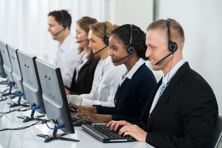 Team Of Businesspeople With Headsets Working In Call Center Office Фото со стока