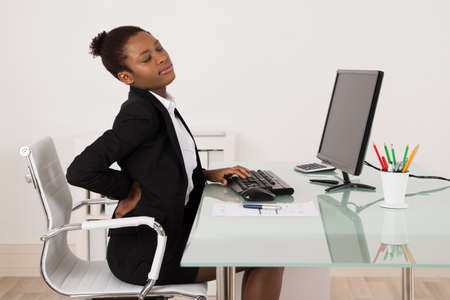 back to work: Young African Businesswoman Suffering From Backache While Working In Office