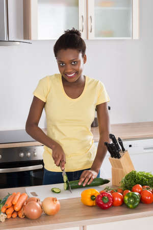 black lady: Young Happy Woman Chopping Vegetables On Chopping Board
