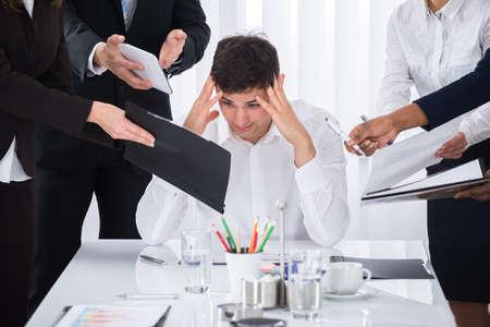 El hombre de negocios joven estresado en el trabajo rodeado por los empresarios