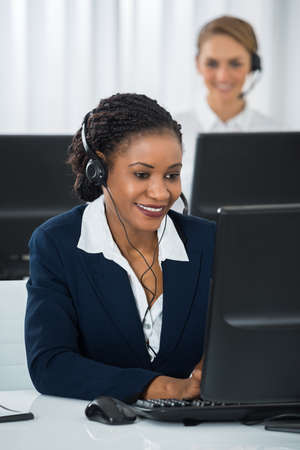 customer service phone: Happy Female Employee With Headset Working On Computer At Desk