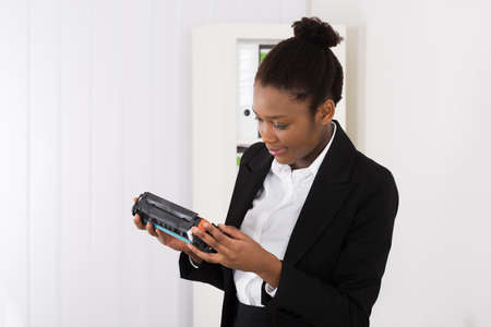 consumable: Young African Businesswoman Looking At Cartridge In Office Stock Photo