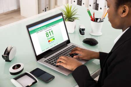 Jeune, africaine, femme affaires, vérification, crédit, note, ordinateur portable, bureau