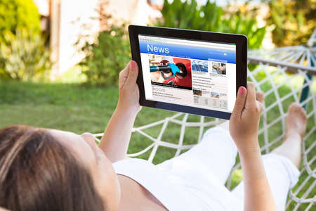articles: Close-up Of Woman On Hammock Reading News On Her Digital Tablet Stock Photo