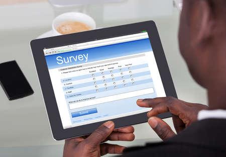 Gros plan d'un formulaire d'enquête de remplissage d'un homme d'affaire sur sa tablette numérique au bureau