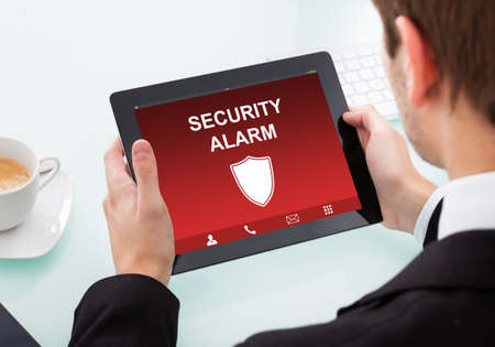 Close-up Of A Businessman Holding Digital Tablet Showing Security Alarm On Screen photo