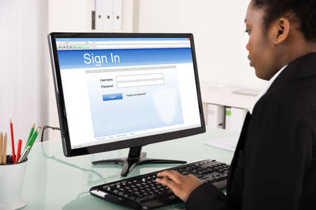 account executive: Close-up Of Young African Businesswoman Signing Into Website On Computer