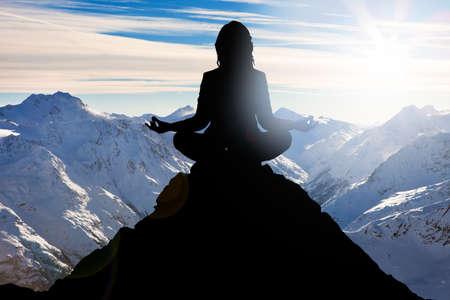 Silhouette di una donna che effettuano yoga sulla montagna di picco Archivio Fotografico