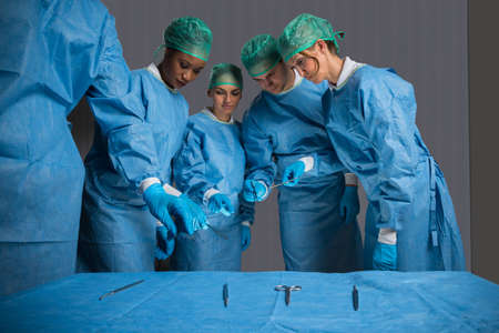work group: Male And Female Surgeons Holding Medical Instruments In Operating Theater