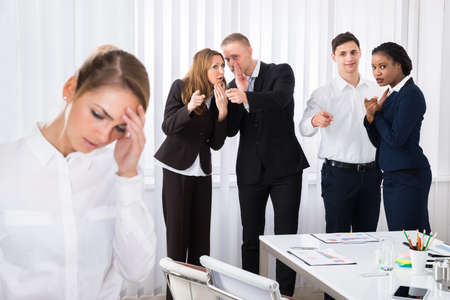 Businesspeople Gossiping Behind Stressed Female Colleague In Office Stock Photo