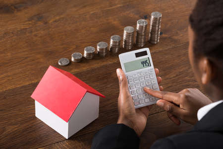 american money: Close-up Of Businesswoman Using Calculator With House Model And Stack Of Coins On Wooden Desk Stock Photo