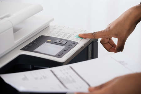Close-up Of Young Businesswoman Hand Operating Printer In Office Archivio Fotografico