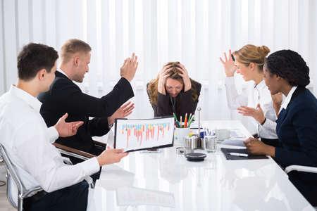 Businesswoman Upset Assis Avec Collègue Aggressive En Réunion Banque d'images